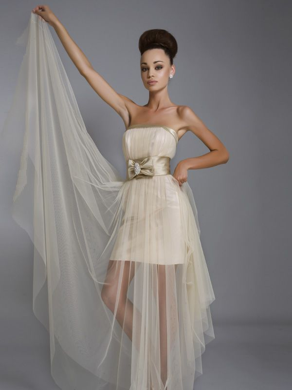 Элегантное открытое свадебное платье с короткой нижней юбкой и длинной верхней, из прозрачной органзы.  Кант из бежевого атласа подчёркивает прямую линию декольте драпированного лифа, широкий пояс с бантом и ювелирной брошью акцентирует талию.