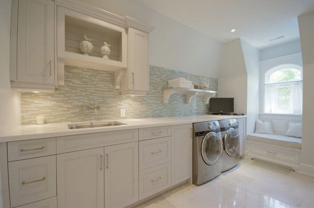 Modern laundry room with crisp white cabinets, marble countertops, blue & gray linear glass tiled backsplash, silver front-load washer & dryer and built-in window seat bench.