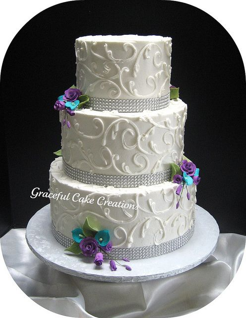 Elegant White Wedding Cake with Crystal Ribbon accented with Teal and Purple Flowers by Graceful Cake Creations, via Flickr