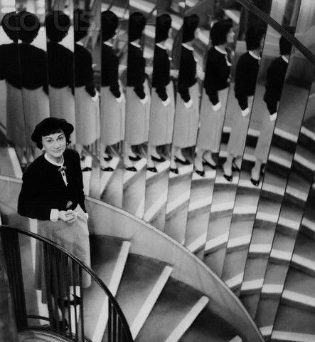 "Gabrielle ""Coco"" Chanel, on the mirrored staircase of her couture house (March 1954)"