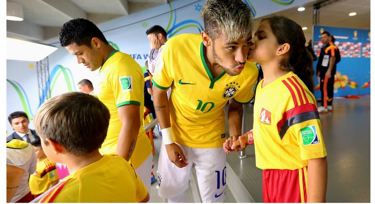 Neymar of Brazil is kissed by a player escort in the tunnel