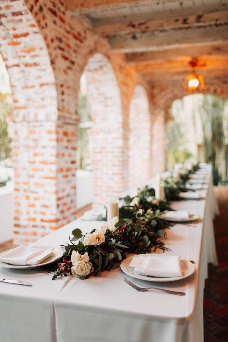 head table is dressed with a lush greenery garland of seeded eucalyptus, silver dollar eucalyptus, and podocarpus that is filled with white roses, burgundy snapdragons and white mums, and peppered with votive and jar candles.