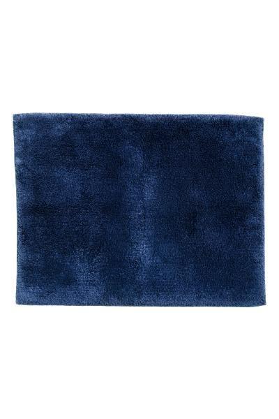 Tapis de bain en coton éponge épais. Modèle avec liséré sur le pourtour et envers anti-dérapant. Ne pas utiliser ce produit sur des surfaces réchauffées.