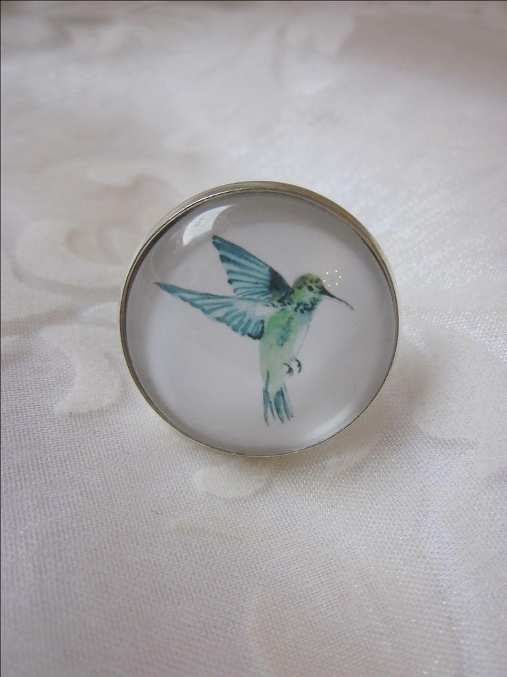 """Cabochon Ring mit Kolibri Vogel Motiv """"Colibri"""" von Madame Floralie  Zauberhafter Ring mit einem Cabochon mit Kolibri-Motiv in Weiß, Türkis und Grün.  Breite des eingefassten Cabochons: 2,5 cm.  Die Fassung besteht aus versilbertem Kupfer.  Der silberfarbene Ring ist verstellbar und kann daher individuell angepasst werden.  Ein außergewöhnliches Schmuckstück, das jeden Betrachter verzaubert."""