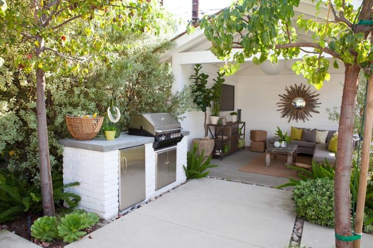 White brick and a concrete countertop make up the outdoor grilling station of this patio. Lush landscape offers plenty of privacy and shade.