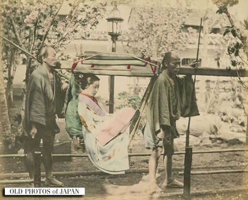 Group portrait of an elegant Japanese woman in a kago (palanquin) carried by two bearers.