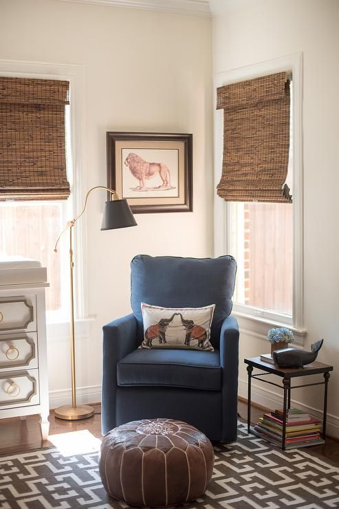 Lovely corner nursing space features a blue nursery glider flanked by windows covered with bamboo roman shades and a brown leather Moroccan pouf atop a brown geometric rug.