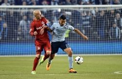Sporting KC mid-fielder Roger Espinoza (27) dribbles the ball against Toronto FC mid-fielder Michael Bradley (4) during the second half at Children's Mercy Park. Sporting KC won 1-0.  #9202566