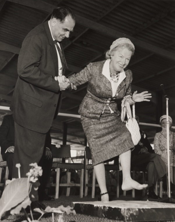 A photograph of Gracie Fields leaving her footprints at Belle Vue in Manchester, taken in June 1959 by Bert Abell for the Daily Herald.    Gracie Fields (1898-1979) leaves her footprints in plaster at Belle Vue gardens an amusement park in Manchester. She is helped by her husband, Boris Alperovici. Fields, real name Grace Stansfield, was an actress, singer and comedienne born in Rochdale, Greater Manchester.