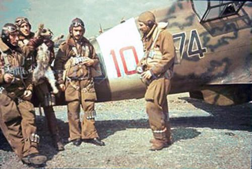 """To avoid bad luck a group of Italian fighter pilots, before the mission, playing with the mascot of their Squadriglia (perhaps 374th Squadriglia) which salute """"romanamente"""" (the Fascist salute) with the right leg. The fighter is a Macchi MC.202."""