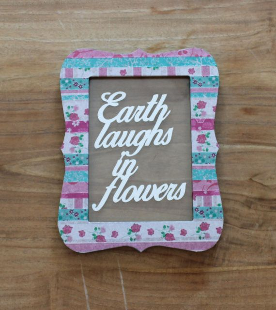 "Papercut art quote in an unique colorful frame; ""Earth laughs in flowers""."