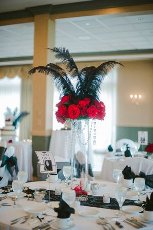 Tall red rose centerpieces with black feathers along with black table linens, decor at an old Hollywood themed wedding reception.