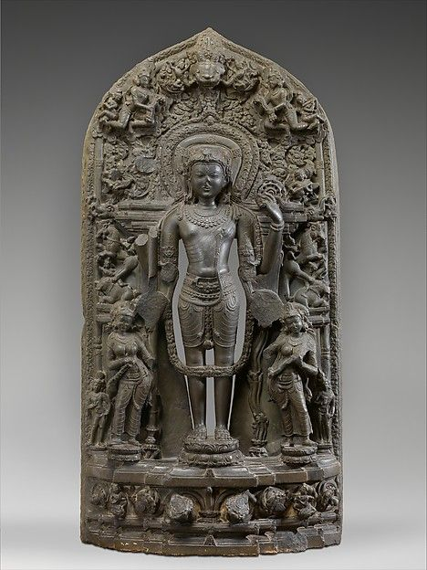 Vishnu stands in perfect symmetry (samapada), the protector of cosmic order. In an iconographic convention unique to medieval Bengal, he is accompanied by the goddesses Lakshmi, holding a fly-whisk (camara) and lotus (padma), and Sarasvati, playing a vina, rather than by his wives Sri Devi and Bhu Devi