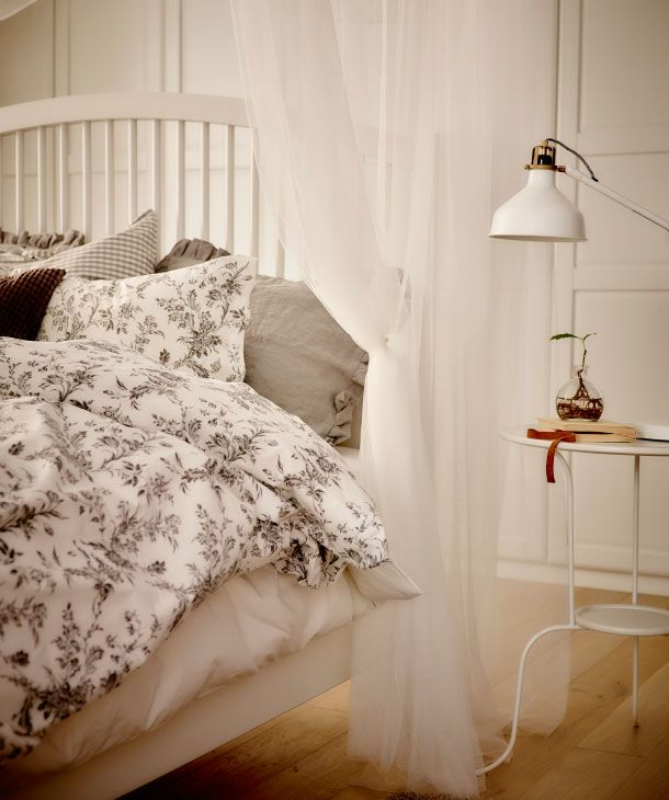 Gi' dit soveværelse et let og roligt udtryk ved at kombinere lysegrå og hvide tekstiler til seng og sofa med florlette hvide tekstiler hængt op i loftet.