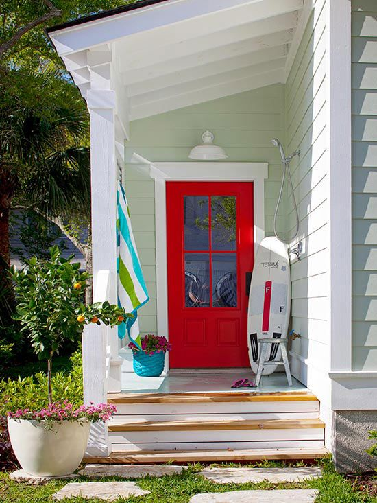 Front Door Style~~Set a colorful tone to your home with a front door decked in a fresh hue. Choose a color that works with your home's existing exterior palette. Here, a juicy red door pairs with pale seafoam green siding, creating a complementary duo. Learn how to paint your door.
