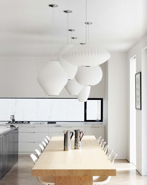 Modern white kitchen dining room. Unique collection of paper lanterns act as a modern chandelier.