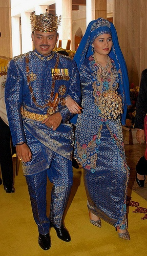 The groom wore a gold crown and a traditional snake-bladed dagger for the ceremony, while his bride was dressed in a blaze of blue and gold. Her glittering Malay outfit was accessorised with drop earrings with diamonds the size of olives and topped by a sparkling tiara.