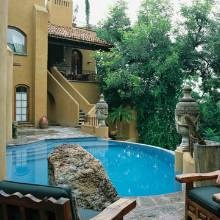 Tucked against the side of a home in San Miguel Mexico, the pool area has the advantage of lush tree-top and garden views. Nearby is a large covered area with curved banco seating.