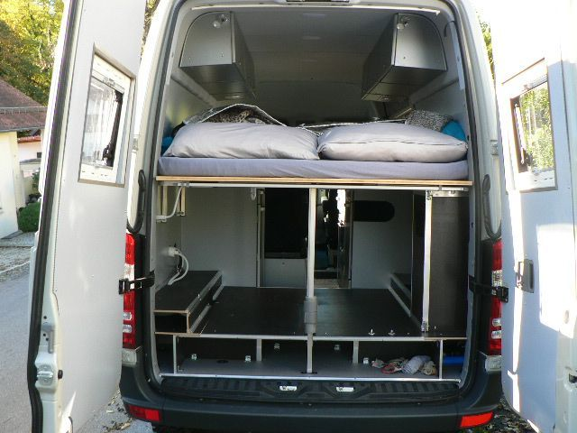 Rear view of the bed and storage in Tom Zwilling's Mercedes Sprinter 316CDI camper van, from the