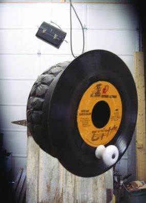 This bird house is made from a wooden bowl painted black and an old 45 record.