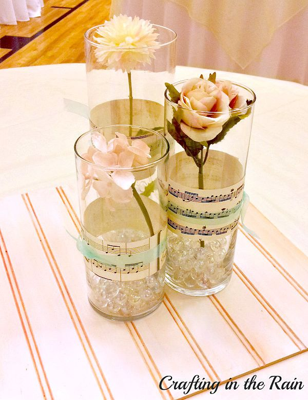Centerpieces. Sheet Music Dyed with Tea and clear marbles in glass cups with different types of flowers