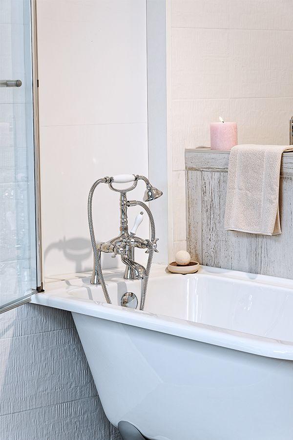 Une baignoire à pieds, une robinetterie rétro, une bougie rose, et ...