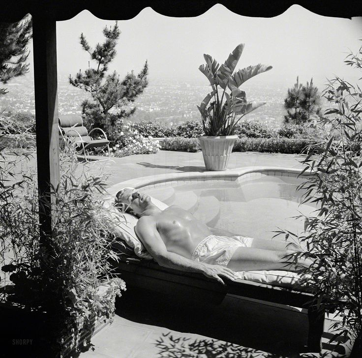 "Los Angeles, 1948. ""Lex Barker regularly suns himself by the swimming pool of friend's home to acquire, keep legendary Tarzan tan.""  / Photo: Maurice Terrell for the Look magazine article ""Princeton-Bred Tarzan."""