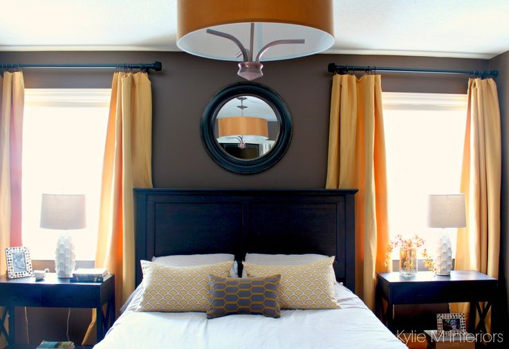 Dark bedroom with gold and yellow accents with dark wood furniture. Benjamin Moore Brown Horse
