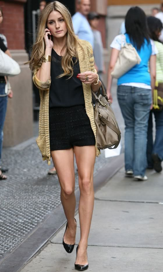 Olivia in a gold cardigan walking around Soho with her german model boyfriend, Johannes.