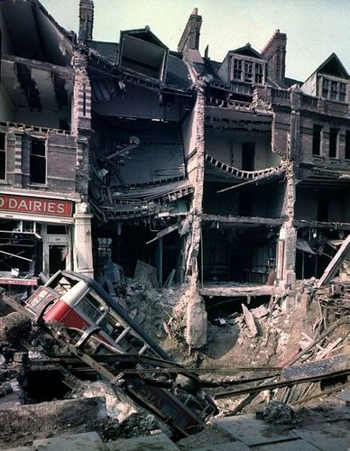 1940 London at War - London Bus 1940 - Wreckage of bus leaning into huge crater in front of bombed out buildings, a result of German aerial blitz attacks during the Battle of Britain.
