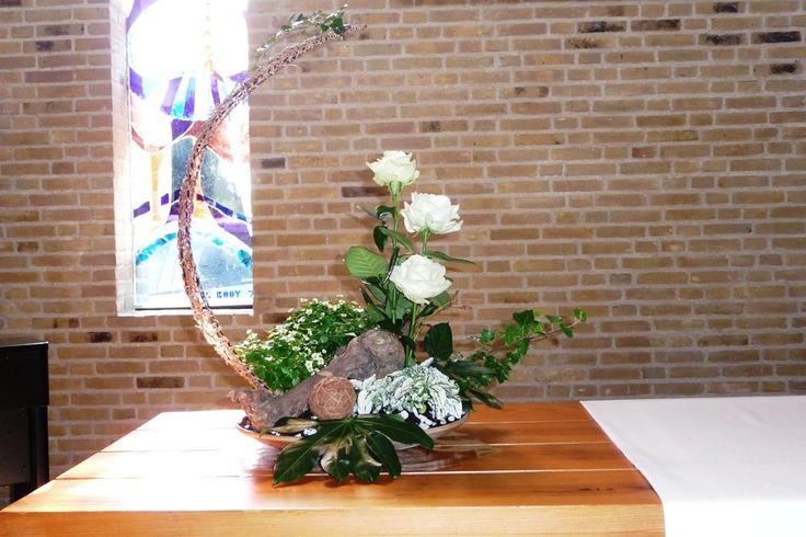 Belijdenis_220511a. De 3 witte rozen staan voor Vader, Zoon en H. Geest, klimop voor trouw en verbondenheid, vingerblad voor de hand van God, gedragen worden. De boog waaronder geborgenheid is.