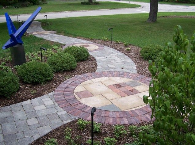 I love this concept... a curvy sidewalk from the driveway to the front door, with an artistic medallion in the middle of it.  I'd only do one large one, not every few feet like they did here... -   Front Walkway Design, Walkway and Path, Bruss Landscaping - Wheaton, IL