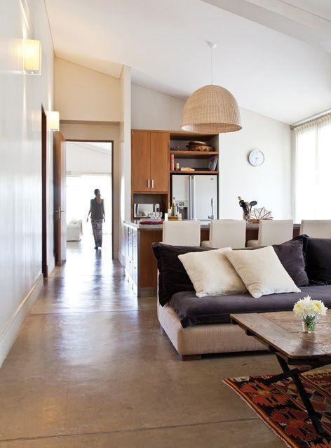 Cocina integrada a un playroom en el que hay un butacón tapizado en arpillera con tachas y colchón de terciopelo, y una mesa-catre de madera.