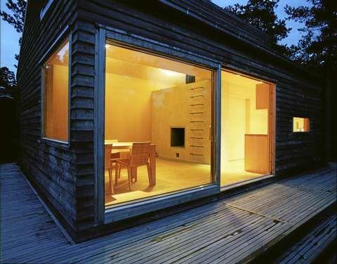 FUNKSJONELT ALLROM: Bak store glassvinduer er allrommet, med peis og trapp opp til hemsen.