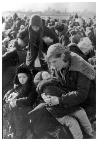 Lubny, Ukraine, A mother with her two children awaiting, with other Jews from the town, at the assembly point, 16/10/1941  Close-up of a young mother with her two children, sitting among a large group of Jews from Lubny who have been assembled for mass execution by the Germans. One of a series of images taken by the German military photographer Haehle, a mem
