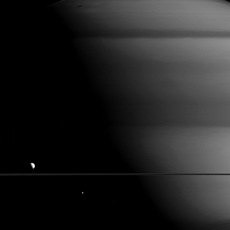 This image shows two moons of Saturn, Mimas on the right and Dione on the left. And though you might find it hard to believe, that dark line running through the center is in fact Saturn's ring.