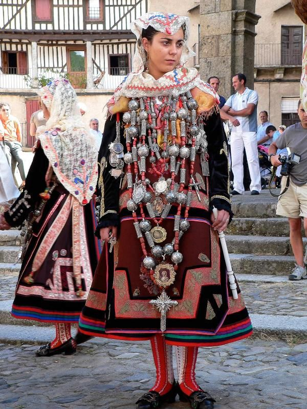 Traje de Vistas de La Alberca, one of the traditional costumes from Salamanca in Leon, a central to northwest region of Spain. This style of dress would have been worn for religious festivals and as wedding attire. Wattle and daub buildings are visible in the background.