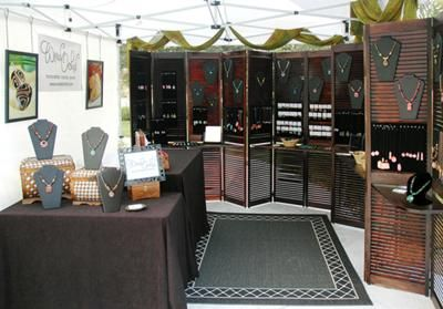 "This craft show booth created by Wired Orchid looks more like a mini shop versus an outdoor booth. I love that she brought in ""homey"" elements to set her booth apart. The shutters are an amazing display idea and the draped fabric from the ceiling is a nice touch."