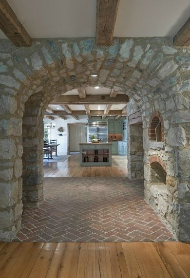 Massive stone archways, brick floors and rustic wooden beams are just some of the fine details found in the new kitchen of this historic farmhouse.  Renovation and expansion of the historic home led by Period Architecture, Ltd. of West Chester, PA.