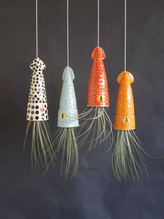 A giant, candy colored squid hanging planter. This amusing planter is strung by steel cables with a loop on the top and in the squid.