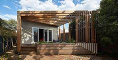 Diseño de pequeña casa de dos dormitorios construida en un lote largo, uso de estantería para definir habitaciones
