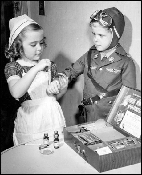 "Kids modelled themselves after adults in World War Two, playing war games and dressing up in smaller versions of the uniforms that they saw all around them. Here Patsy Ann McHugh, as a nurse, bandages the hand of ""wounded aviator"" Bobby O'Connor with her nursing kit in New York."
