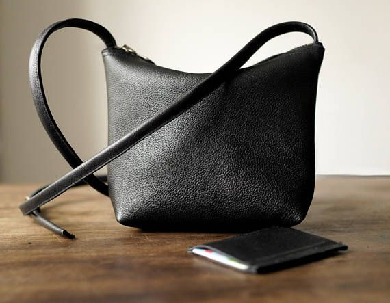 A small, elegant, minimal crossbody bag. Holds whatever you may need it to hold, phone, coin purse, card holder, usb, a few keys, etc. Made of genuine soft black leather. Close with zip. No lining. Adjustable strap. Leather card holder in the set. Dimesions: height: 16 cm/ 6,2 witdht top: 18 cm/ 7,1 depth bottom: 5 cm/ 2 strap : 120 cm/ 47,2  Possibly to make in other colours. Feel free to write to me. Ready to ship in 2-3 working days.  Standard delivery time:  European ...