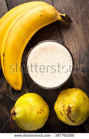 Glass of smoothie and fresh bananas and pears on wooden background. Close up