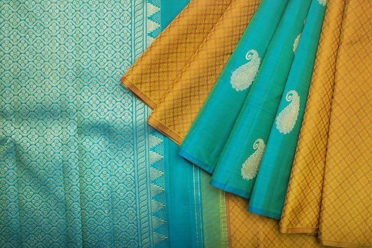 Kanakavalli Mustard Yellow Kanjivaram Saree with self design and no border. The Pleats and Pallu are in blue colour. Pallu is having mangoes