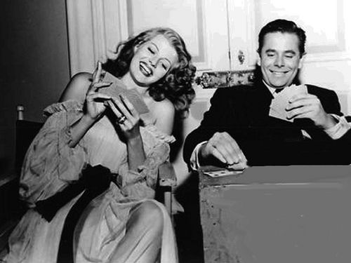 Actors Rita Hayworth and Glenn Ford play cards during a set break for the 1946 production of Gilda.