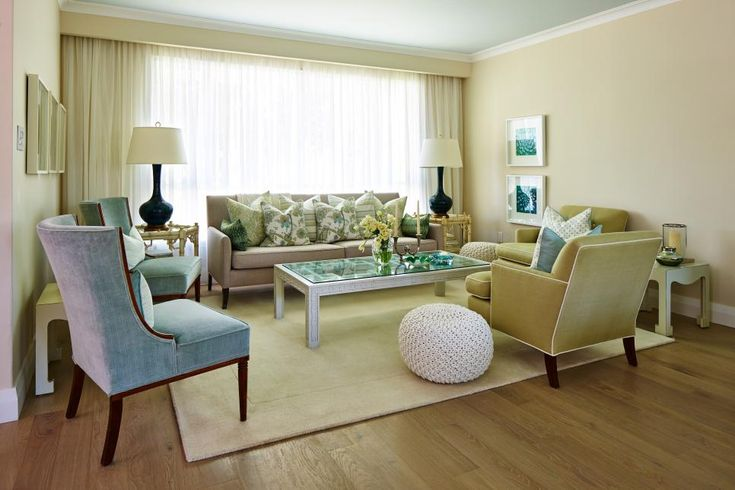 As seen on season one of Sarah Sees Potential, two walls were removed to allow this chic, transitional living room to flow seamlessly into the adjoining kitchen and dining room. Sarah chose vintage furniture in muted blues and greens to fill the neutral space and framed the large window with a custom-built cornice and sheer retractable curtains.