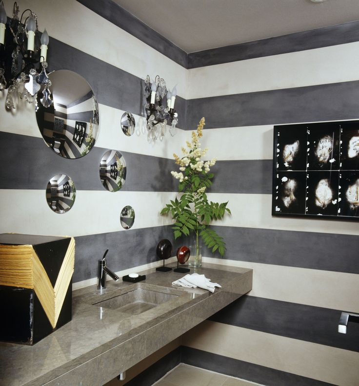 Alternating stripes of gray and white paint enliven the powder room of a modernist home in Geneva, which was decorated by Alexandra de Garidel-­Thoron of the Swiss design studio Thébaïde. A constellation of convex mirrors appears to float above the stone sink.   - ELLEDecor.com