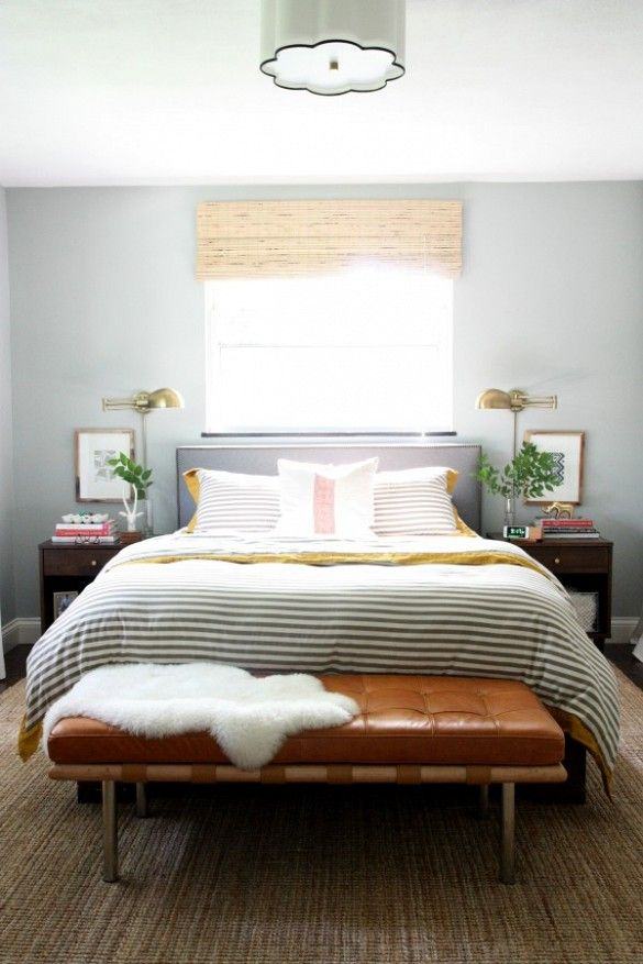 Layered bedroom design with stripe duvet and leather tufted bench.