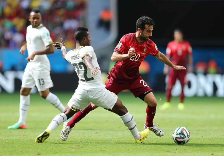 Wakaso Mubarak of Ghana an Ruben Amorim of Portugal compete for the ball during the 2014 FIFA World Cup Brazil Group G match between Portuga...